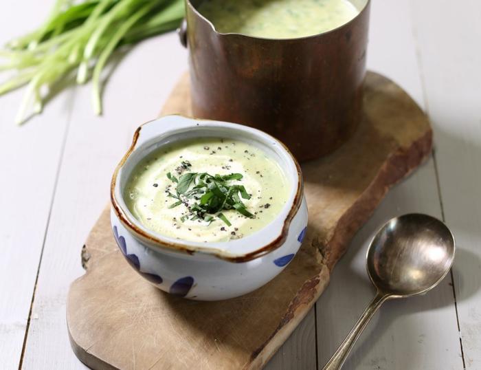 brett aus holz eine weiße schüssel mit suppe mit bärlauch und sahne ein löffel
