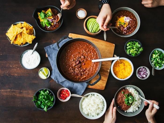 brett aus holz hände mexikanisches gericht paprikaschoten chilischoten chili con carne rezept