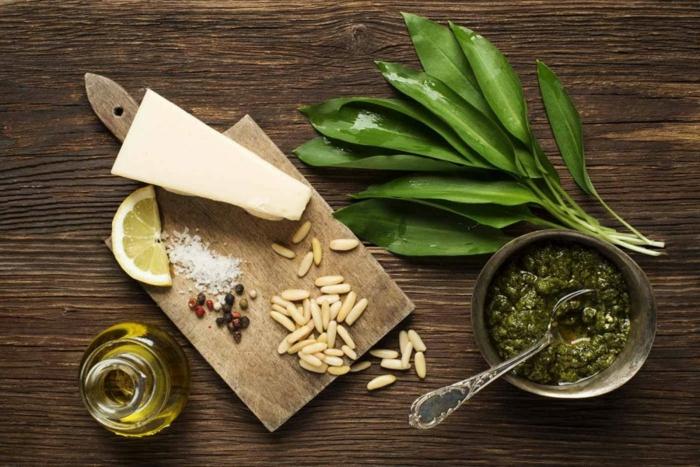 die zutaten für bärlauch pesto grüne bärlauch blätter zitrone parmesan und öl