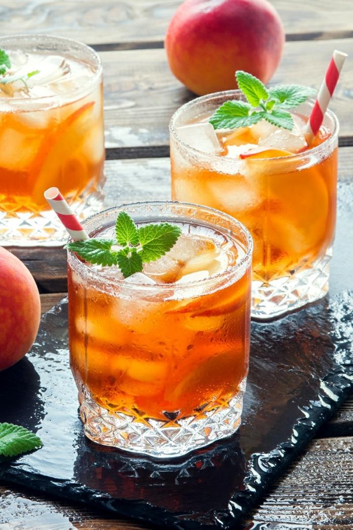 drei gläser mit eistee mit frischer pfefferminze und eiswürfeln kleine strohhalme pfirsich eistee selber machen