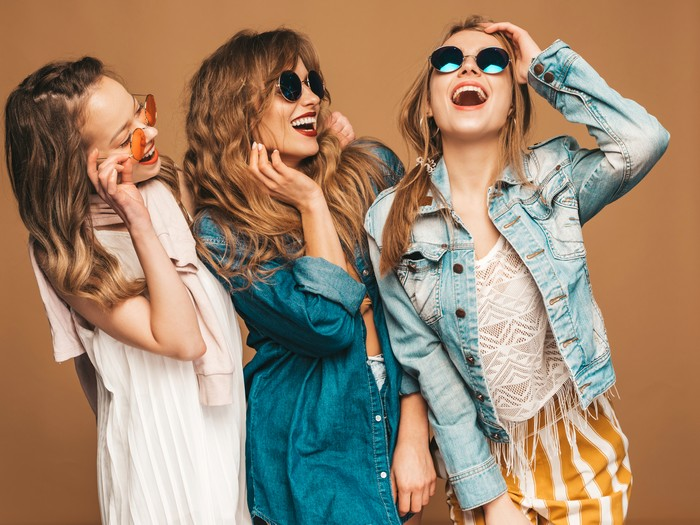 three young beautiful smiling hipster girls in trendy summer casual jeans clothes. sexy carefree women posing near golden wall. positive models going crazy in sunglasses