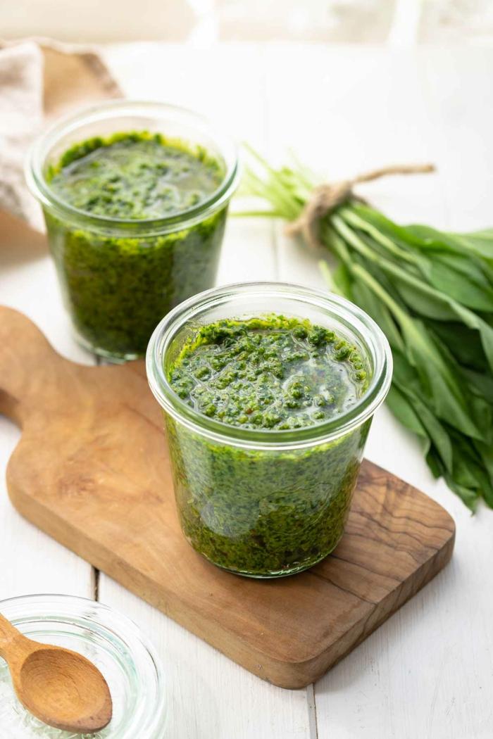 ein brett aus holz rezepte mit bärlauch ein glas mit grünem pesto mit bärlauch