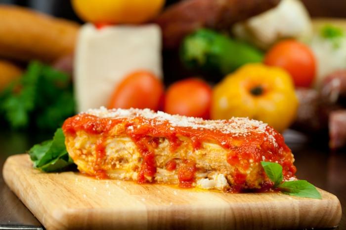 ein brett aus holz und ein stück lasagne mit tomaten sße und parmesan geschmolzenem käse