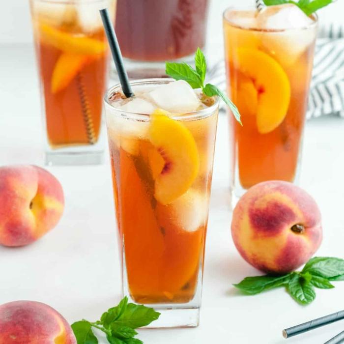 ein glas mit einem schwarzen strohhalm geschnittene pfirsiche und eiswürfel