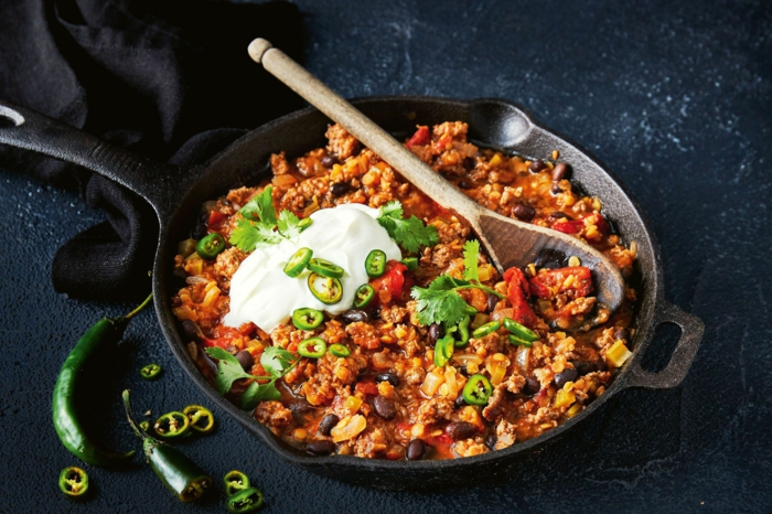 ein löffel aus holz ein top mit einem mexikanischem gericht mit lauch chili und paprikaschoten fleisch