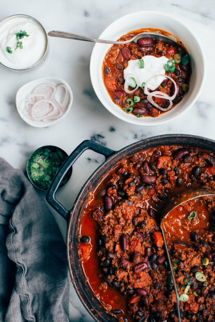 ein löffel ein topf mit einem mexikanischem gericht mit mais und bohnen und fleisch chili con carne rezept original