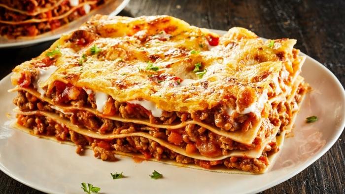 ein stück lasagne mit hackfleisch und käse lasagne selber machen rezept tomaten und petersilie