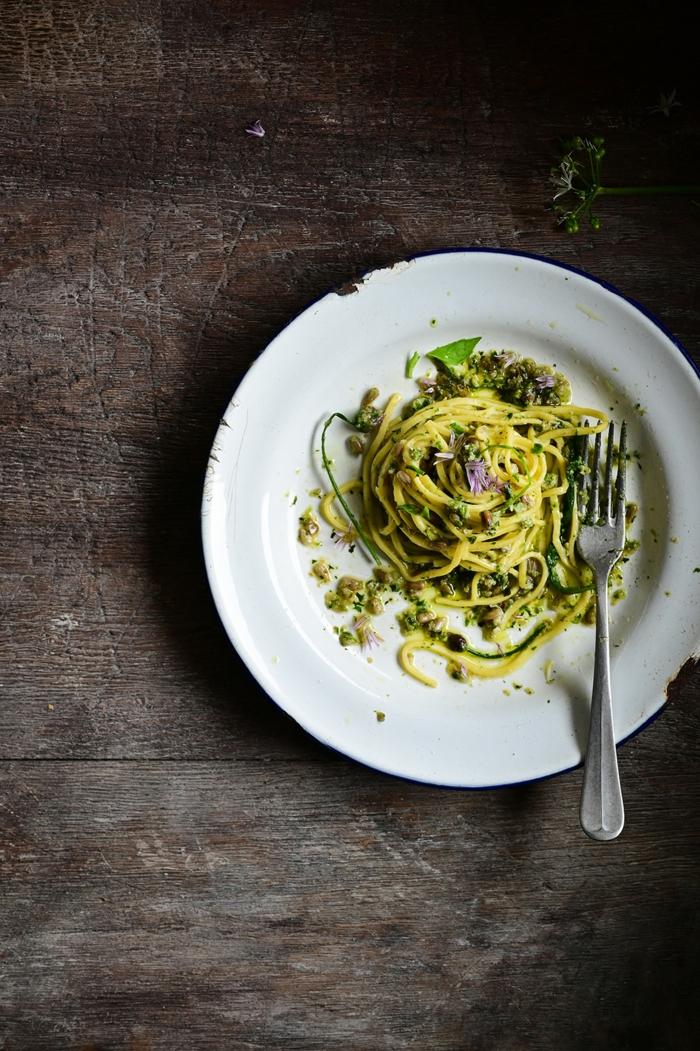 ein tisch aus holz ein weißer teller mit pasta mit grünem pesto eine gabel