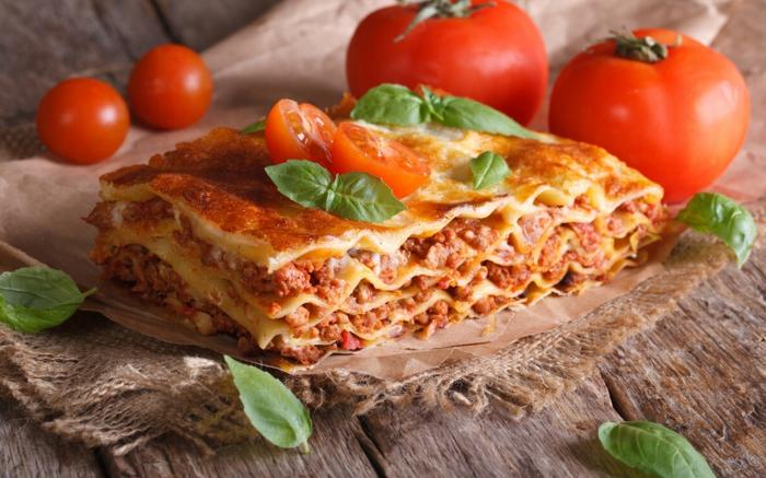ein tisch aus holz frische tomaten und basilikum blätter eine lasagne mit fascjiertes und käse