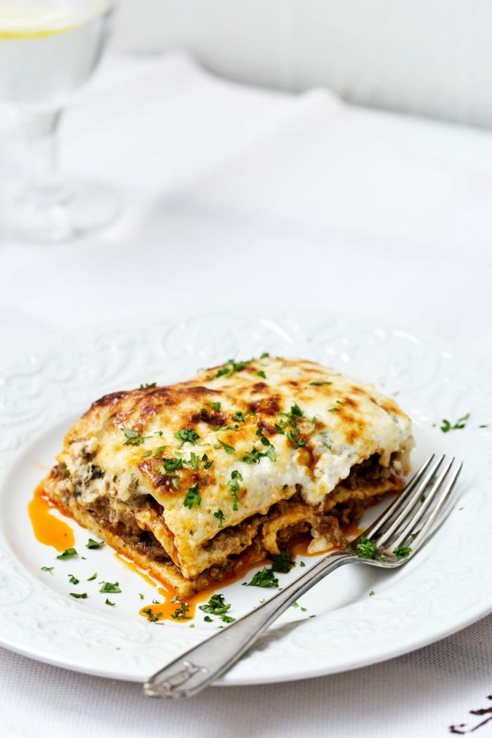 eine gabel und ein teller mit veganer lasagne mit spinat und petersilien blättern