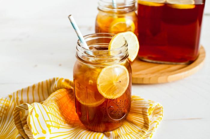 eine gelbe decke eistee selber machen rezept ein glas mit einem pfirsich eistee und geschnitenen zitronen