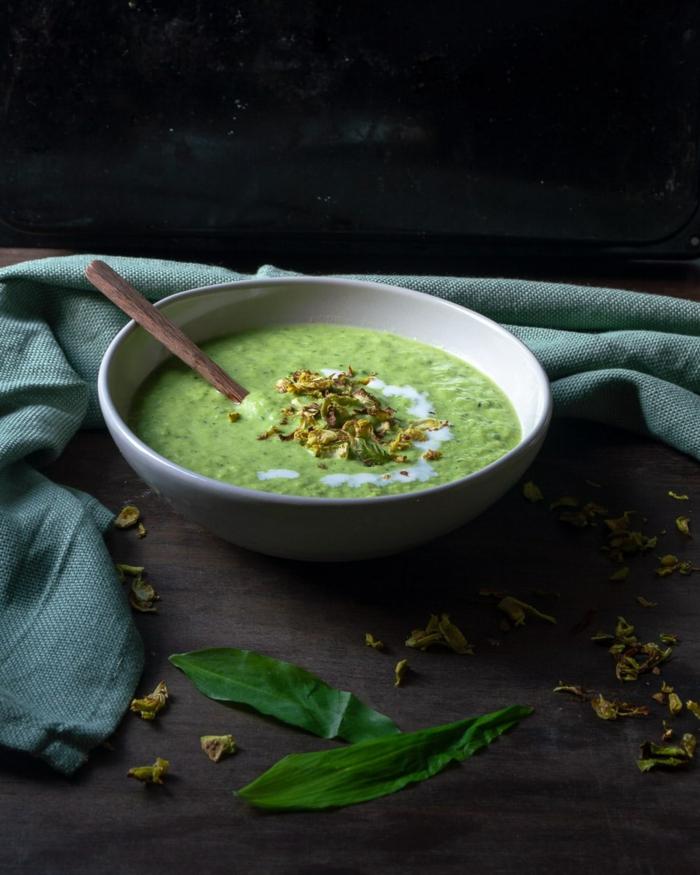eine grüne vegane passierte suppe mit bärlauch eine weiße schüssel mit sahne suppe mit wild garlic