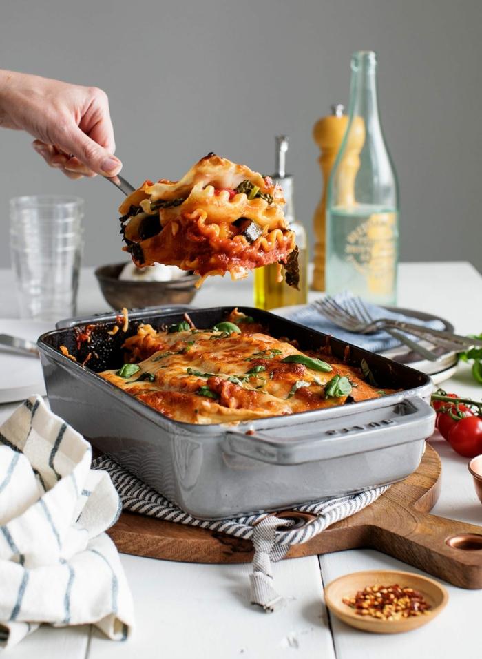 eine hand mit gabel mit lasagne lasagne selber machen rezept ein brett aus holz