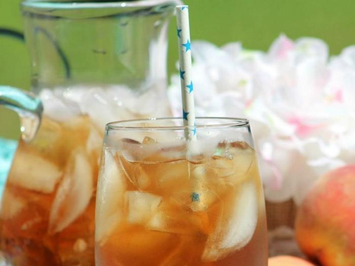 eine kanne und ein glas mit eiswürfeln und eistee ein strohhalm