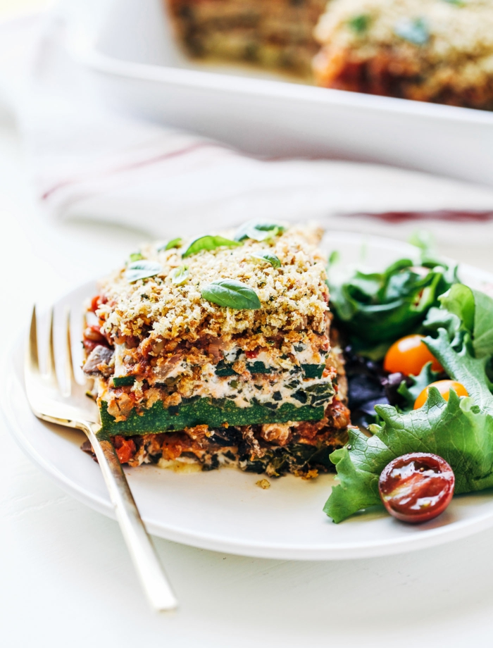 eine vagene lasagne mit spinat und salat ein weißer teller eine gabel