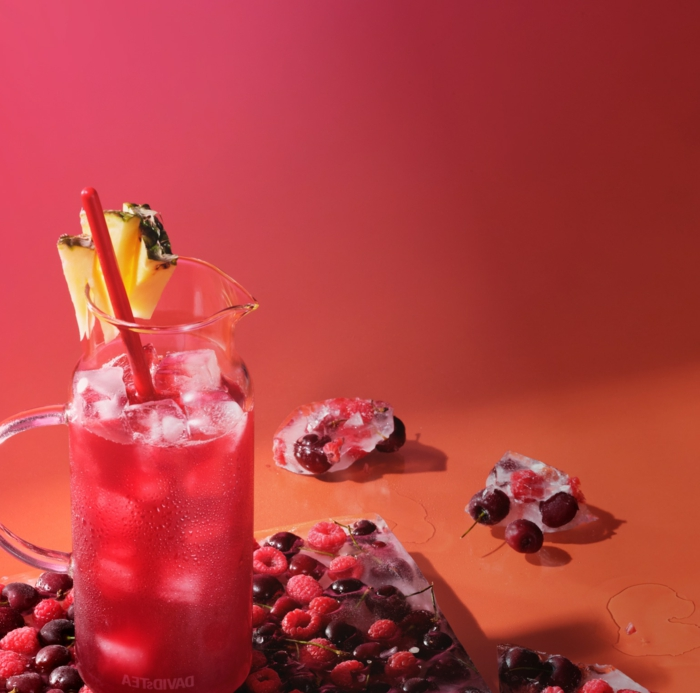 eistee selber machen rezept ein glas mit eistee und eiswürfeln und einem strohhalm und zitronen