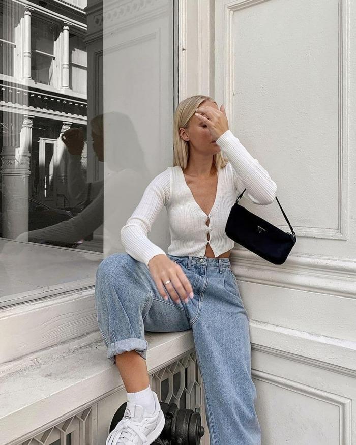 elegante weiße bluse mit knöpfen frau mit kurzen blonden haaren hellblaue jeans damen slouchy schnitt schwarze mini tasche