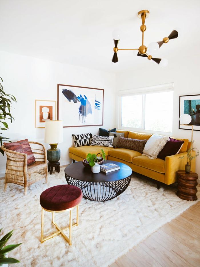 eleganter gelber sofa deko kissen schwarzer kaffee tisch weißer flauschiger teppich gemälde an die wand wohnzimmer skandinavischer stil