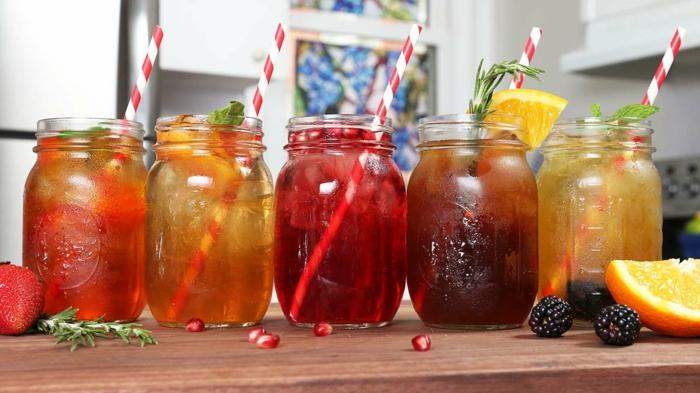 fünf gläser mit verschiedenen eistees gläser mit roten und orangen eistees geschnittene zitrone und erdbeere