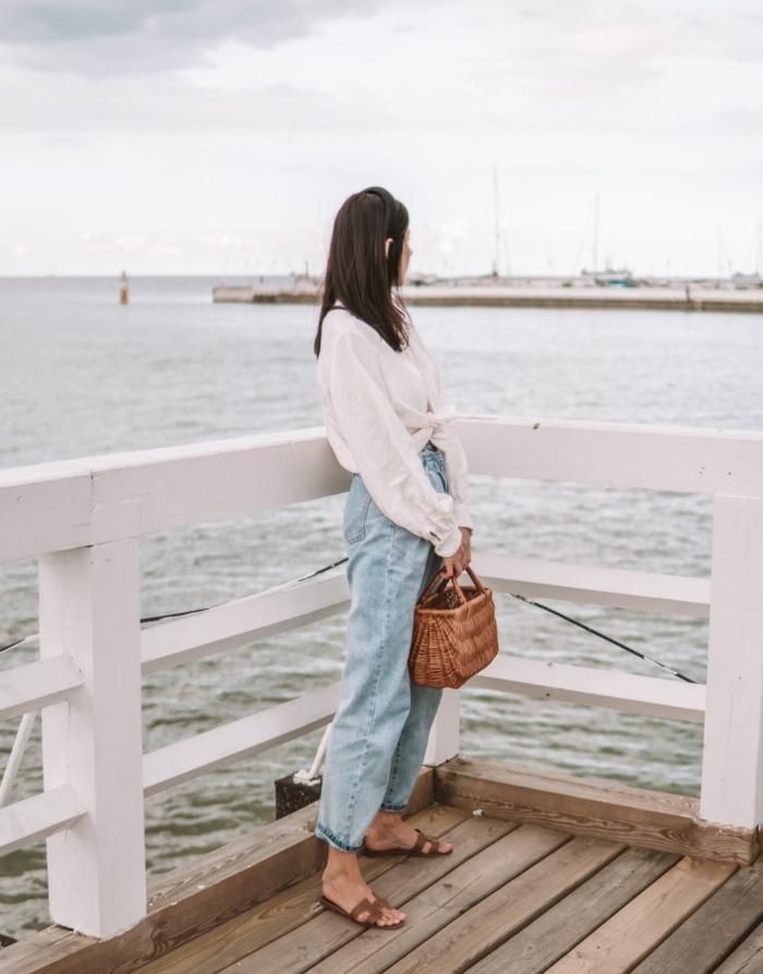 foto am meer sommer outfit chic weiße bluse mit langen ärmeln kleine korbtasche slouchy jeans mit hohem bund