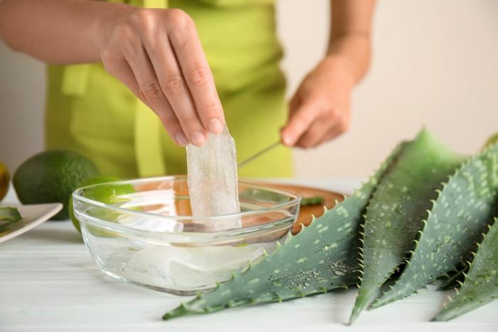 frau entfernt gel aus einer aloe vera pflanze aloe vera für haare diy rezepte ideen schönheit tipps
