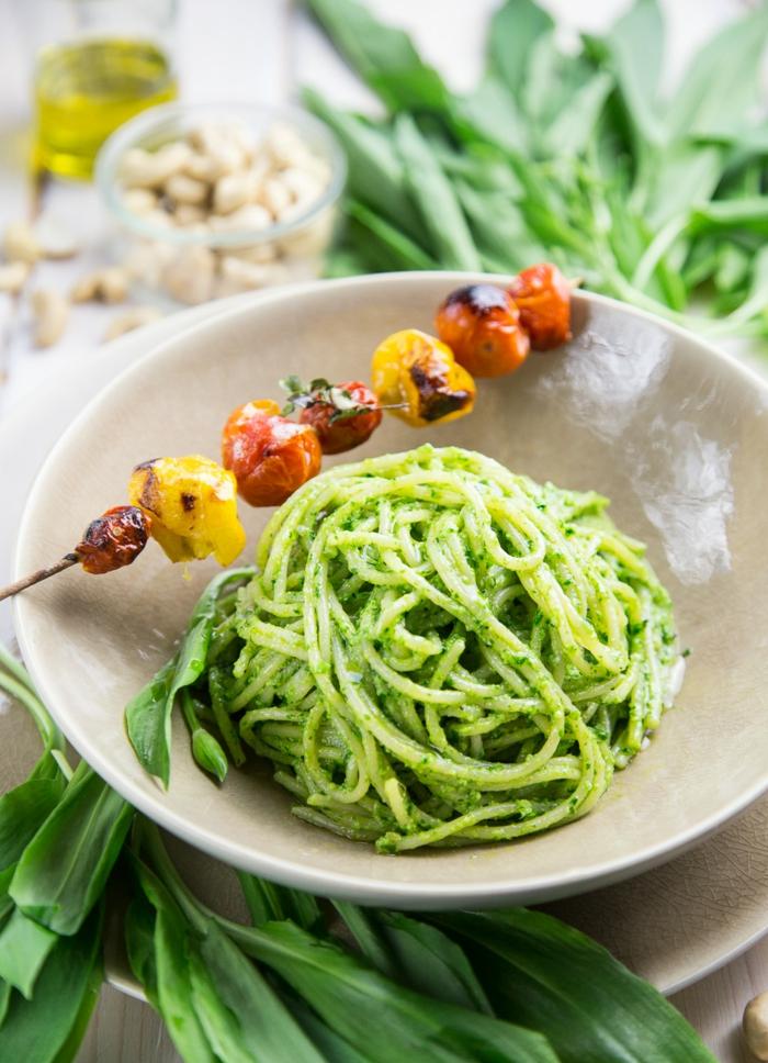 frische bärlauch blätter weißer teller mit spaghetti mit pesto zutaten für bärlauch spaghetti
