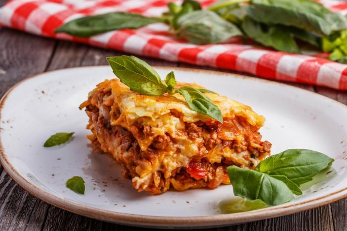 frische basilikum nlätter und eine lasagne mit faschiertes und tomaten ein weißer teller