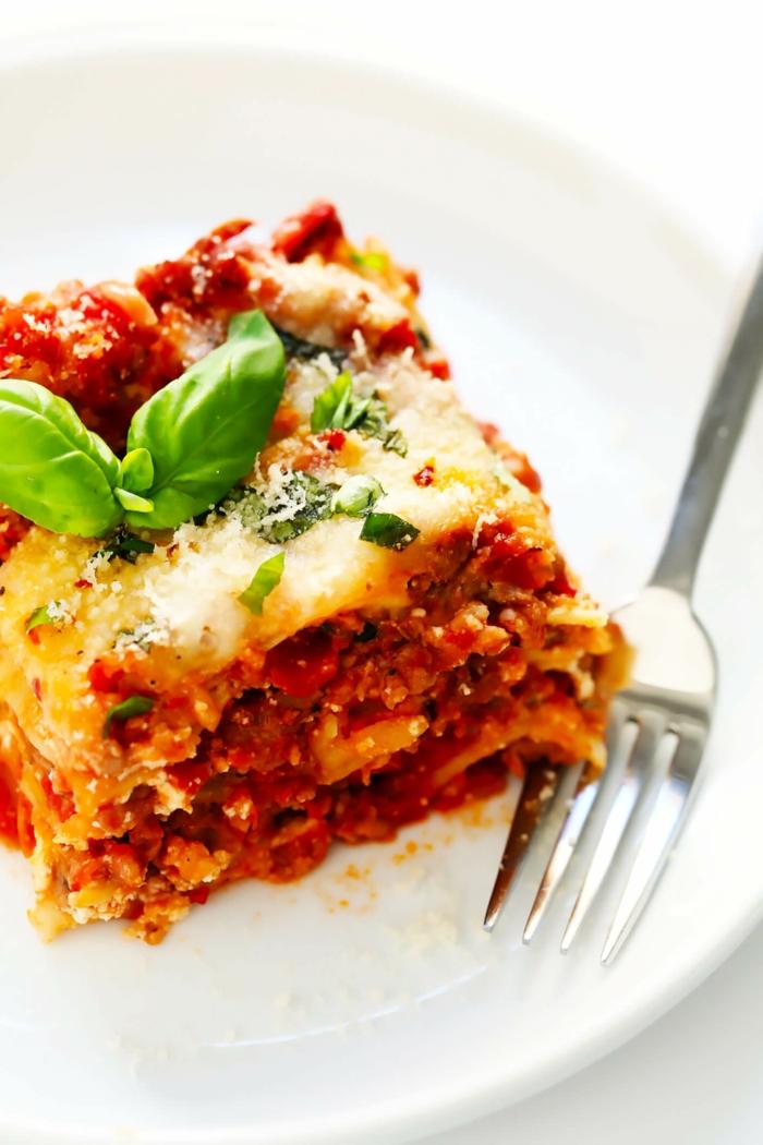 gabel und lasagne mit tomaten soße faschiertes und käse ein weßer teller