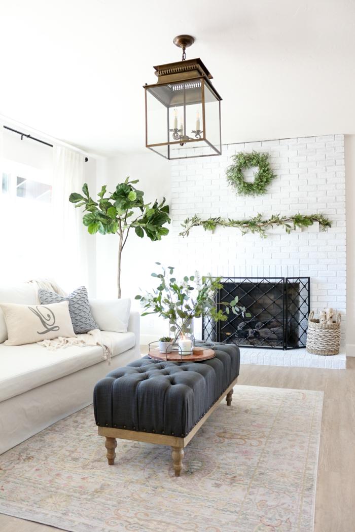 gemütliches großes wohnzimmer hygge möbel blaue liege in der mitte des zimmers weißer sessel große und kleine deko pflanzen weiße backsteinwand