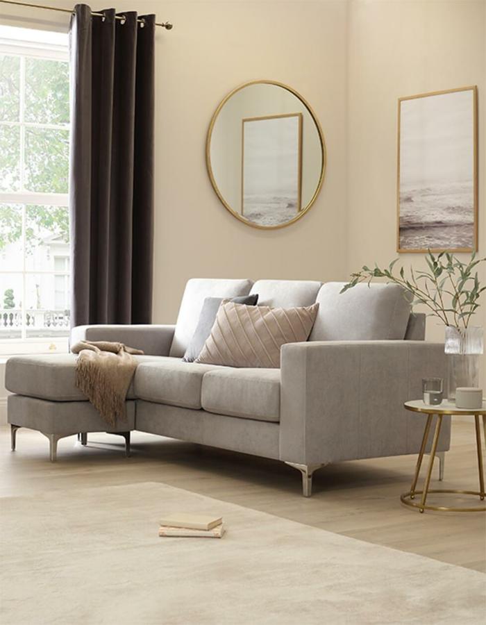 gemütliches hygge wohnzimmer in neutralen farben kleiner ecksofa grau beiger teppich runder spiegel an die wand deko kissen hygge wohnen