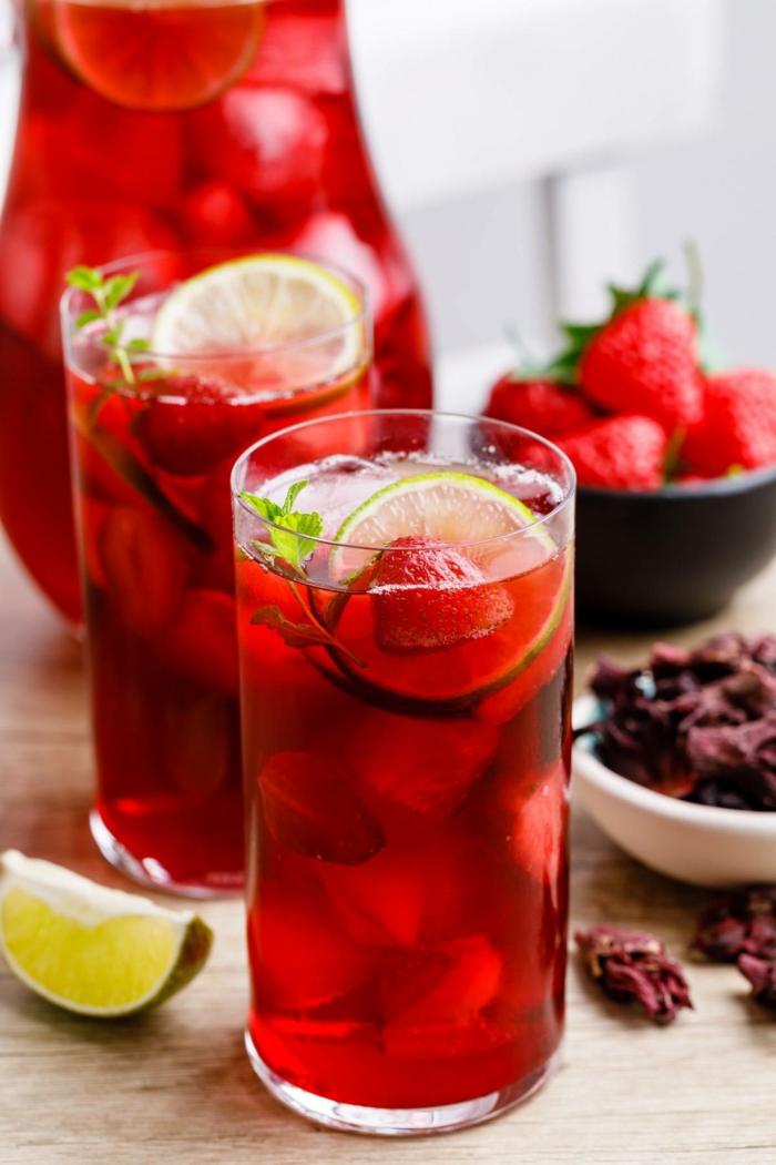 geschnittene zitrone zwei gläser mit rotem eistee und eiswürfeln erdbeere eistee