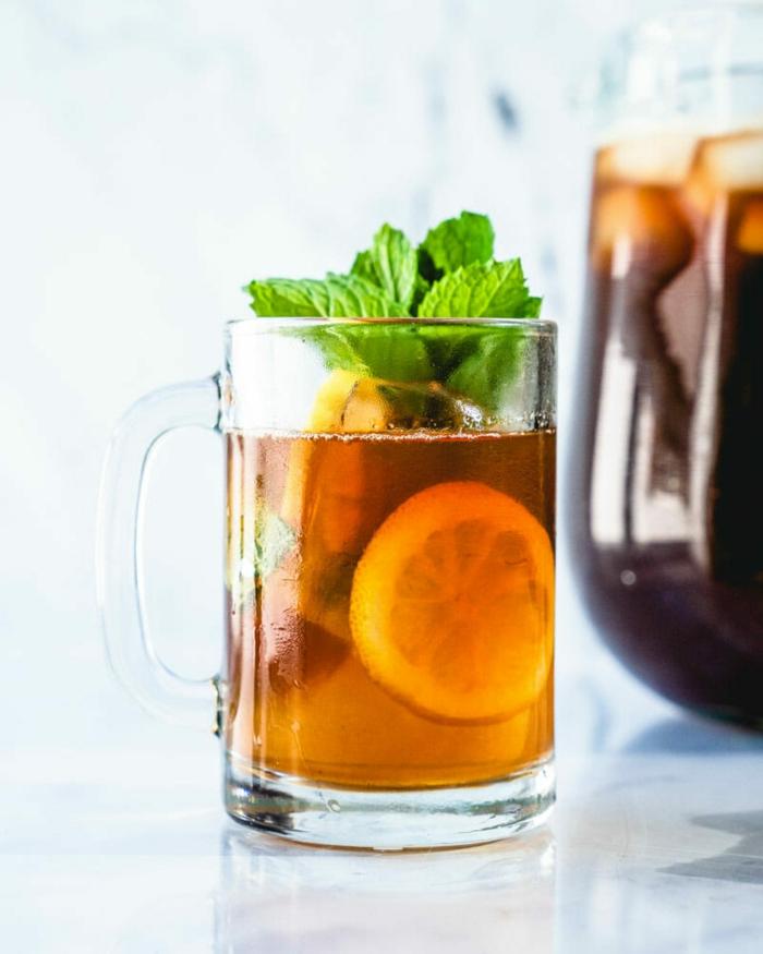 glas mit einem eistee aus schwarzem tee und pfirsich und geschnittenen zitronen frische pfefferminze