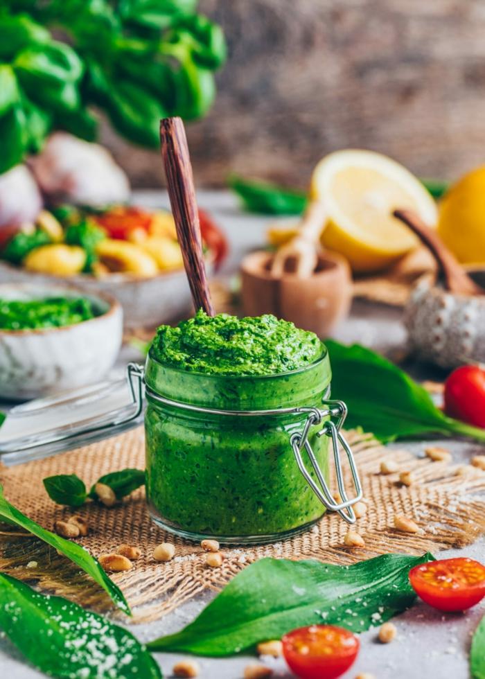 glas mit grünem bärlauch pesto frische geschnittene tomaten ein brett aus holz geschnittene zitronen bärlauch rezepte
