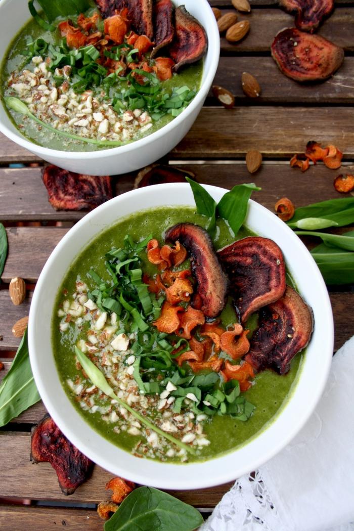 grüne suppe mit möhren und sahne und bärlauch ein tisch aus holz zwei schüssel