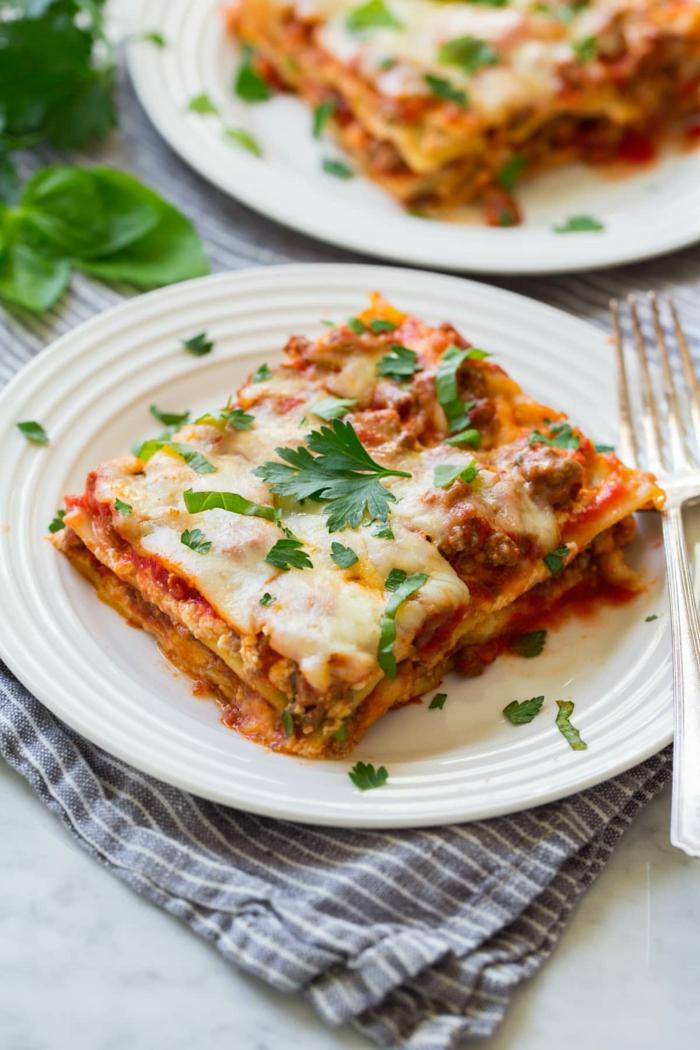 graue decke lasagne selber machen rezept ein weißer teller mit lasagne mit geschmolzenem käse und frischen petersilien blättern