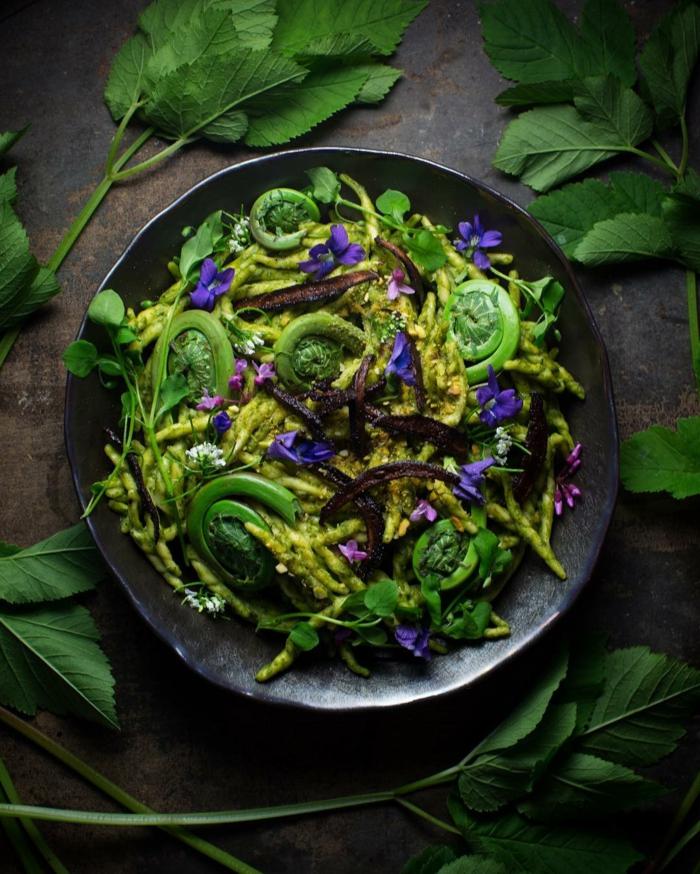 grauer teller mit einem grünen salat mit bärlauch und violetten blumen