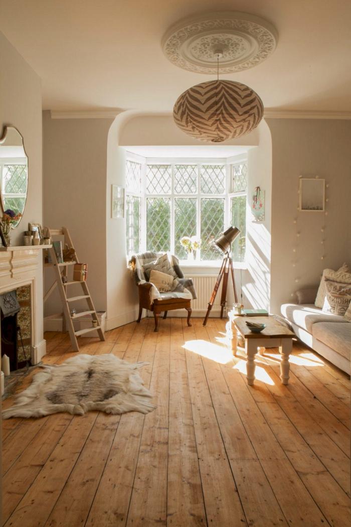 große fenster mit weißen rahmen holzboden wohnzimmer hygge möbel minimalistische schlichte einrichtung flauschiger kleiner teppich