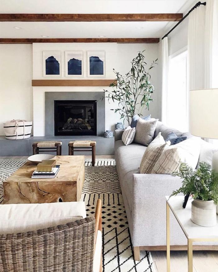 großes wohnzimmer skandinavischer stil großes sofa grau mit deko kissen großes kamin großer tisch aus holz