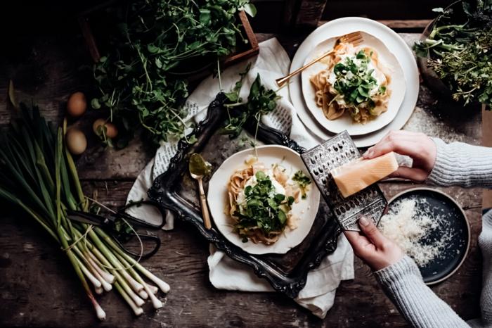 hände einer frau bärlauch rezepte zwei weiße teller mit veganen spaghetti mit bärlauch