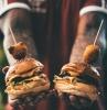 hände eines manns mit tattoos zwei große hamburger mit geschmolzenem käse