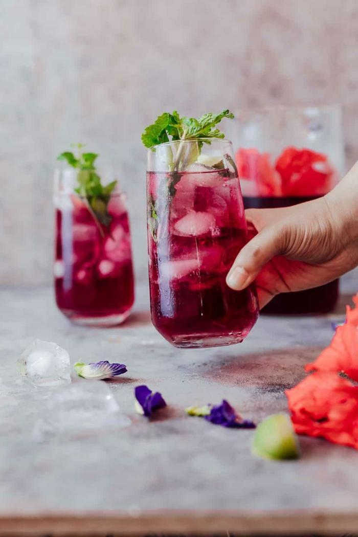 johannisbeeren eistee selber machen rezept eine hand mit einem glas mit eistee