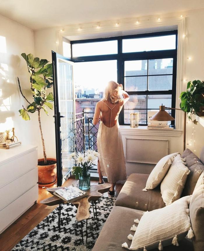 junge frau im langen kleid hygge style schwarz weißer teppich große grüne pflanze skandinavische inneneinrichtung kleines wohnzimmer fenster mit schwarzen rahmen