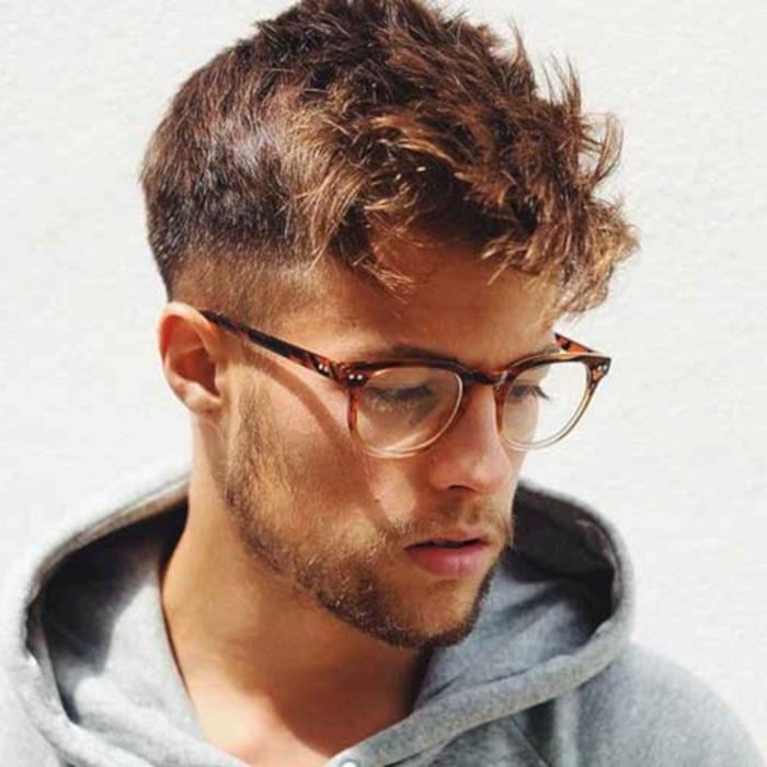 junger mann mit runden braunen brillen grauer sweatshirt moderne männerfrisuren kurz und lang