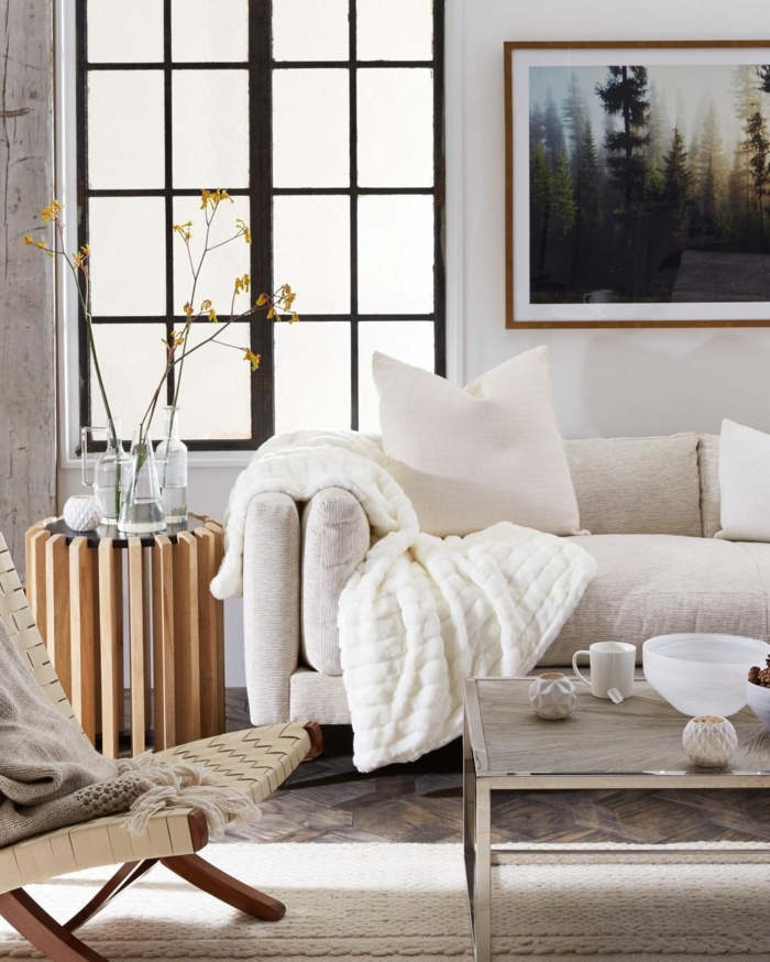 kleiner runder tisch aus holz weißes sofa und kuschelige decke schönes gemälde an die wand was ist hygge interior design 2021