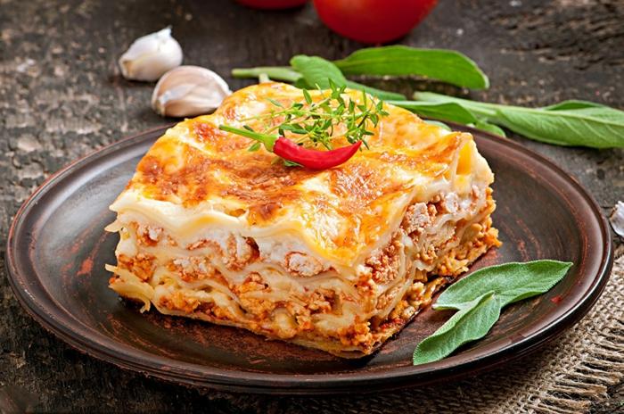 knoblauchzehen und zwiebeln ein teller mit lasagne mit frischen tomaten und parmesan