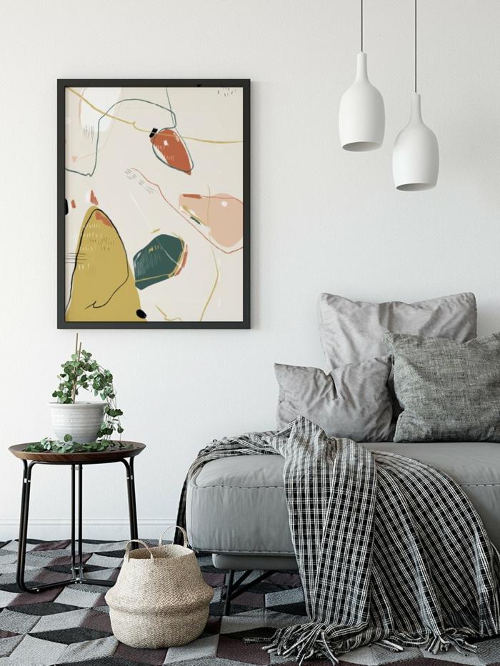 kretaives farbiges gemälde an die wand graues sofa und kissen runder tisch mit kleiner grünen pflanze hygge einrichtung