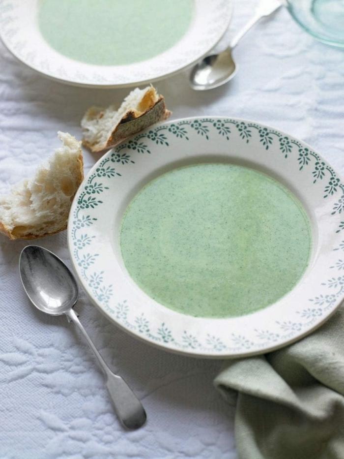 löffel aus metall brot ein weißer teller mit grüner suppe eine decke vegane suppe