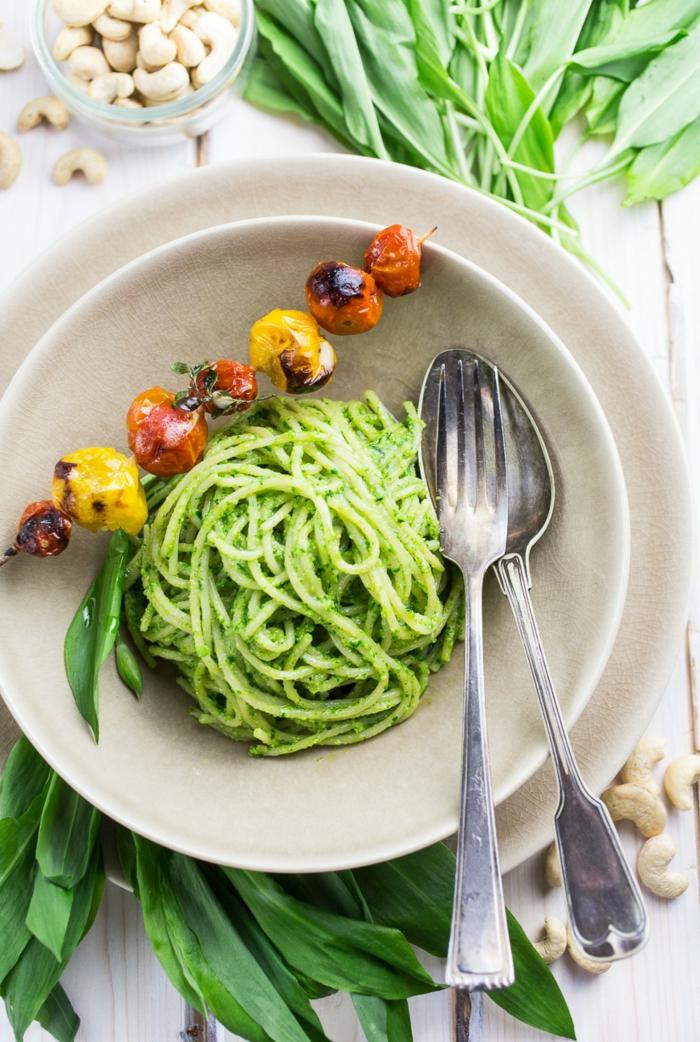 löffel und gabel ein weißer teller grüne spaghetti mit bärlauch gesund