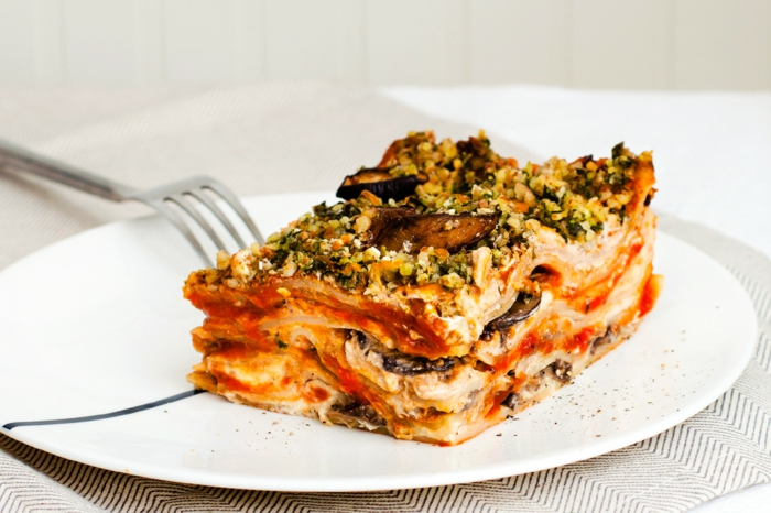 lasagne mit spinat und aubergine ein weißer teller eine gabel