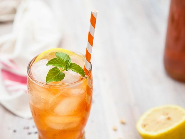 mango eistee selber machen rezept ein glas mit orangem getränk und eiswürfeln und minze